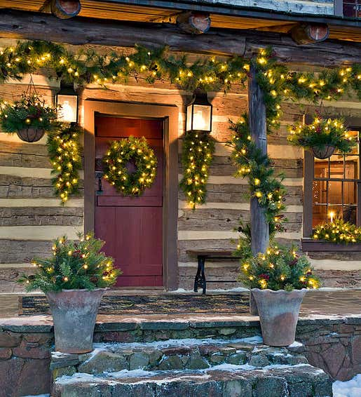 Image of Blue Ridge Pre-Lit Holiday Greenery on a Porch. Shop Holiday Greenery